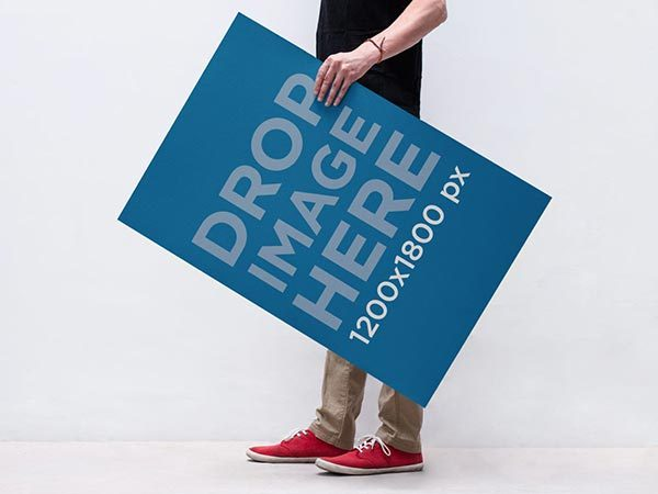 Free PSD Poster Mockup of a Man Holding a Poster